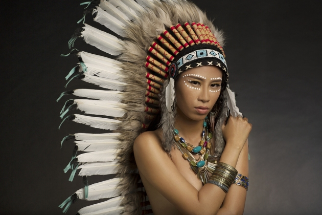 Girl wearing Native American Indian headdress and jewelry and face paint